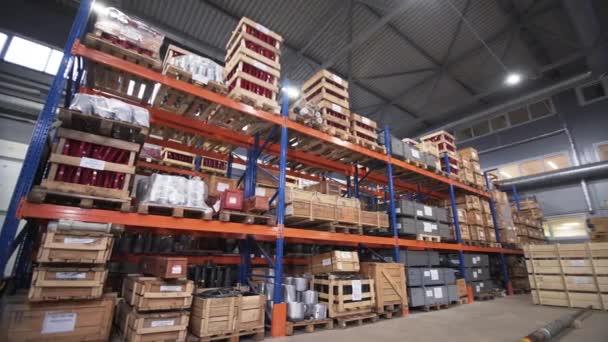 Lager mit Regalen und Regalen, gefüllt mit Holzkisten auf Paletten. Vertriebsprodukte. Logistikgeschäft. Im Inneren ein großes Lager mit hoch gestapelter Fracht. Schriftliche Markierung auf Schachteln