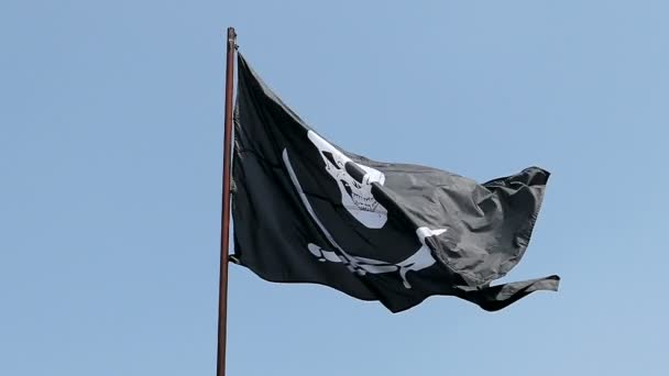 Slow motion. Pirate flag waving in wind against blue sky.