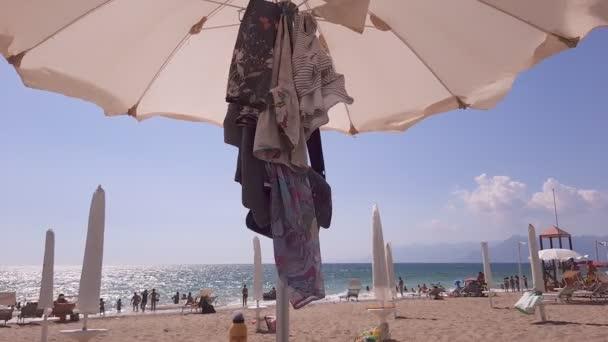 Pontecagnano, Italien. 19. August 2020. Einige Kleider hängen unter einem Schirm, der im Wind weht, mit blauem Himmel und Menschen am Strand.