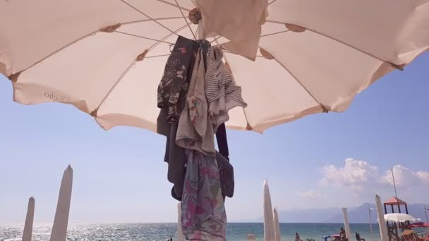 Pontecagnano, Italien. Einige Kleider hängen unter einem Schirm, der im Wind weht, mit blauem Himmel und Menschen am Strand.