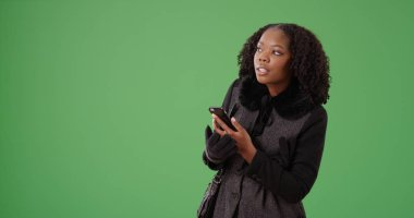 Casual black female with cellphone looking around for someone on green screen