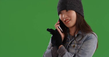 Cute Chinese female in denim jacket and beanie chatting on phone on green screen