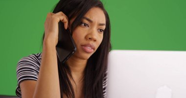Close up of black woman talking on cellphone using laptop on green screen