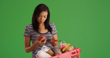 African American woman out grocery shopping examining produce on green screen