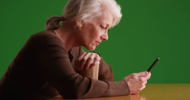 Profile of mature white woman sitting using mobile device on green screen