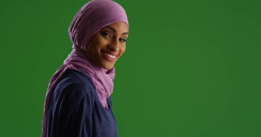 Young black woman in purple headscarf smiling at camera on green screen