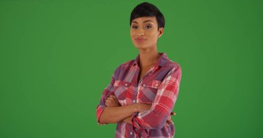 Portrait of black female in flannel with arms crossed on green screen