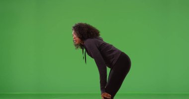 Profile of black athletic female taking break from workout on green screen