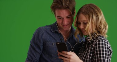 Portrait of young couple using phone to listen to music together on green screen
