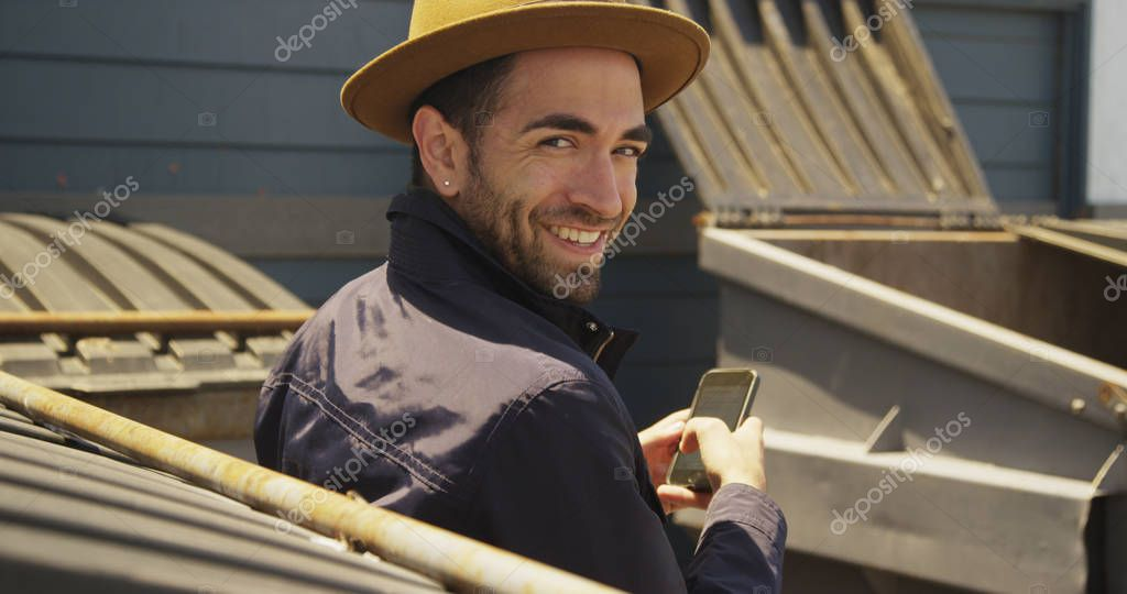 Happy Hispanic man using smartphone outdoors