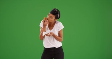 Stylish black female eating a slice of delicious cheese pizza on green screen