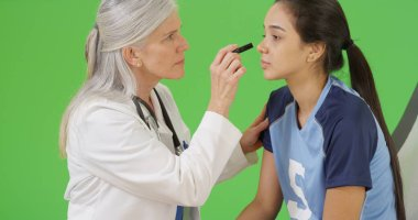 Young concussed soccer player is checked for dilated pupils on green screen