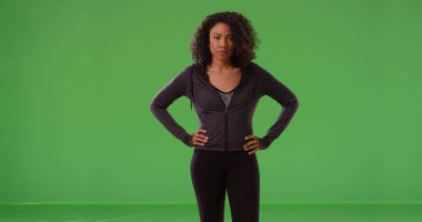 Active black sportswoman posing confidently with hands at hips on green screen