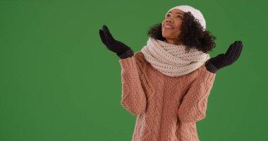 Black millennial female in winter attire enjoying snowfall on green screen