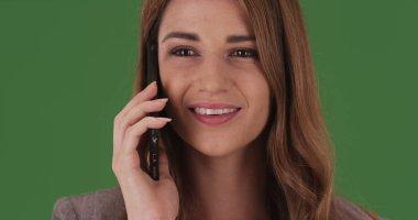 Beautiful businesswoman talking on smartphone on green screen