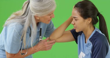 A medical professional attends to an injured soccer player on green screen