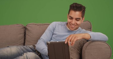 Young Hispanic man sitting on couch using tablet computer on green screen