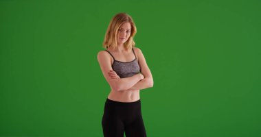 Fit young lady in sportswear with arms crossed looking at camera on green screen