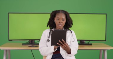 Black female doctor using tablet near computers with green screen displays