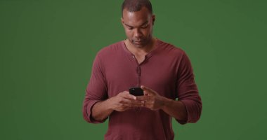 A black man texts on his mobile phone on green screen