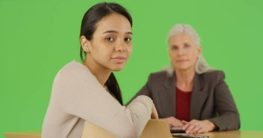 Millennial latina looks at the camera sitting at meeting table on green screen