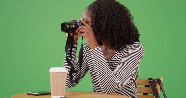 Black female photographer taking picture with camera at cafe on green screen