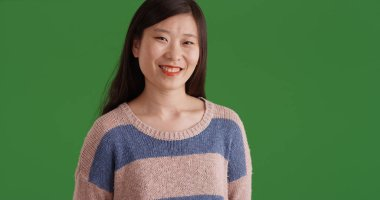 Happy young Asian woman wearing sweater smiling on green screen
