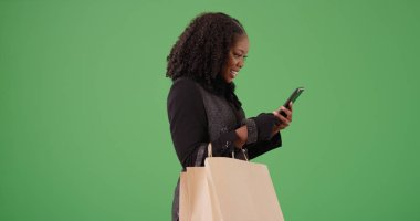 Black woman in her 30s texting on phone holding shopping bags on green screen