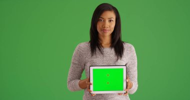 Smiling black woman holding tablet with green screen for custom content