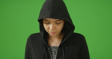 A depressed young girl in hoodie poses for a portrait on green screen