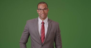 A black businessman poses for a portrait on green screen