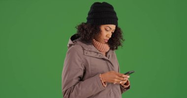 Young African American woman in winter clothing texting on phone on green screen