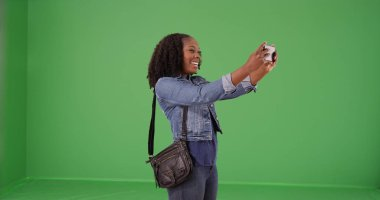 Young African American woman taking selfie with phone on green screen