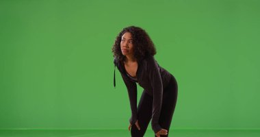 Young black woman runner taking break during workout on green screen