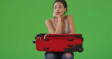 Traveling millennial Hispanic girl waits for her ride on green screen