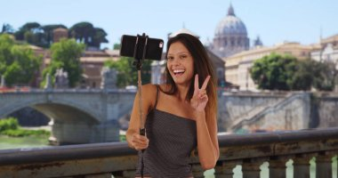 Young tourist woman on bridge in Rome taking selfies near St Peters Basilica