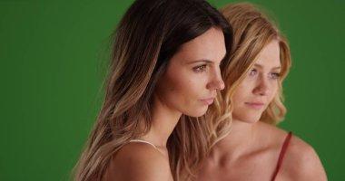 Portrait of two beautiful white women looking off screen on green screen