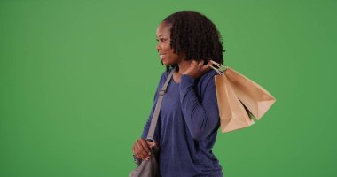 Black woman with shopping bags looking at item she wants to buy on green screen