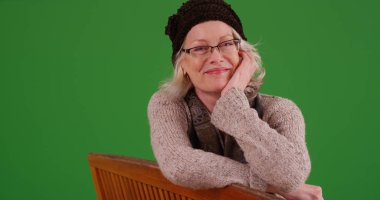 Sweet old Caucasian lady sitting on bench smiling at camera on green screen