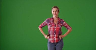 Middle aged Caucasian woman gardener posing on green screen
