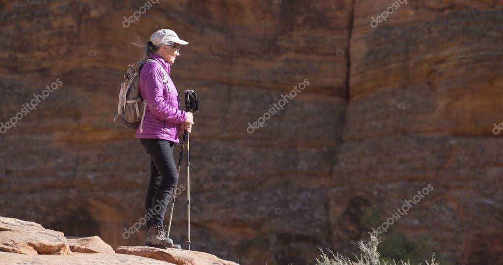 Happy senior female hiker standing on cliff with trekking staffs admiring nature