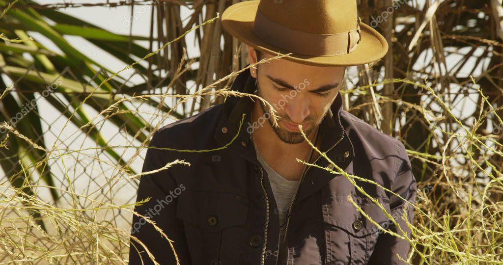Hip Hispanic man using smartphone outdoors