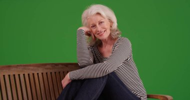 Charming old white female posing happily on bench on green screen
