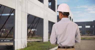 Rear view of handsome and serious architect at construction site