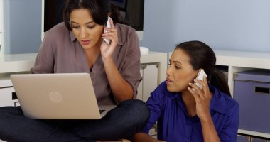 Black and Hispanic business women working together while talking on mobile phones