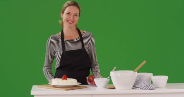 Cheerful Caucasian woman by counter with baking supplies on green screen