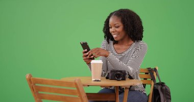 Smiling African American woman texting on smartphone at cafe on green screen