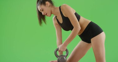 Fit Latina girl lifting weight on green screen