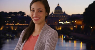 Pretty Latina female stands near St Peters Basilica at night smiling