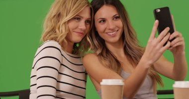 Attractive white females at cafe sitting and taking selfie on green screen